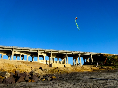 Kite is waggling in the sky, in front of the coast highway bridge.